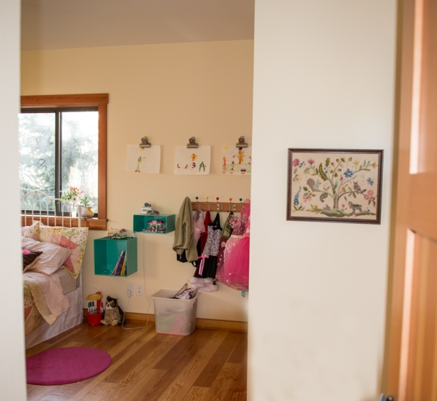looking into her room, her great grandmother's embroidered art hangs on wall into her room